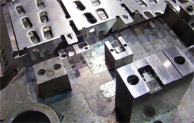 use of channels milled directly withn the die plate and protected with carefully machined steel covers