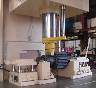 Shown is a travelling-gantry straightening press, with x-y axis movement. The traveling carriages support the shaft and are hydraulically operated to raise and lower the shaft off of and on to the V-blocks.